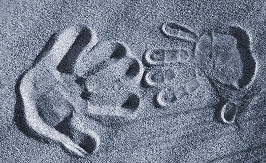 Handabdrücke im Sand monochrom