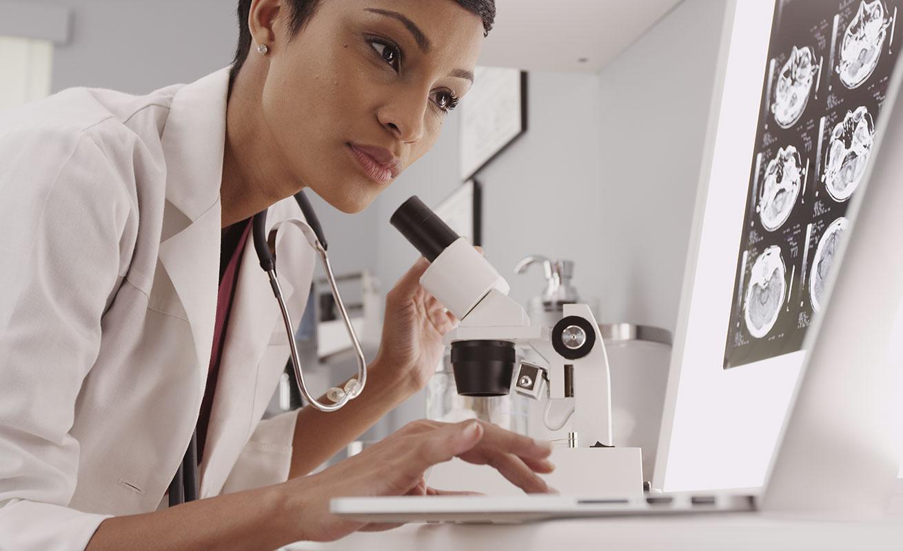 Ärztin mit Mikroskop und Labtop